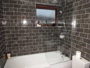 Bathroom with shaped glass shower screen and tiles