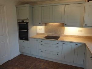 Pale green painted kitchen units with bespoke granite worktops