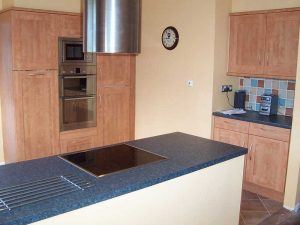 Central kitchen island with extractor fan above induction hob