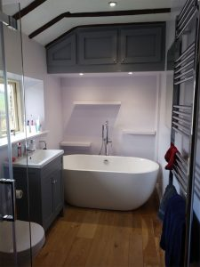 Grey painted bathroom with bespoke carpentry for wall units and vanity unit